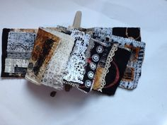 Ineke Berlyn textile art book in neutral colours, bound with beads onto a piece of driftwood