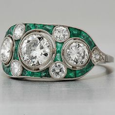 Art Deco engagement ring with European-cut diamond and emeralds in antique style is crafted in lavish platinum, weighs 4.8g and measures 10mm wide and 4mm deep.