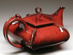 Beautiful and uniquely-shaped red ceramic teapot by Magnum Pottery.