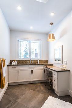 Salle de bain des invités, plancher effet béton, comptoir en quartz gris avec des éclats dorés, dosseret importé doré/or et vanité blanche.