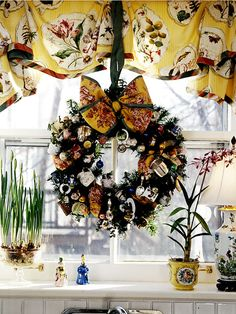 This creative kitchen wreath is a fun way to display a unique collection. To begin, purchase an evergreen wreath, which can be found at garden shops, roadside tree stands, and even home-improvement stores during the holidays. Next, attach a bow the coordinates with the room where you'll hang the wreath and wrap it around several times. Next, add family collectibles to the wreath; to camouflage the attachments, use green-coated florist wire. Finally, finish off the wreath with fresh greenery.