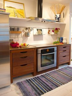 This kitchen was featured in DIY Network.com.  This counter is equipped with side drawers, providing a clever way to maximize space in a tiny kitchen.  Where cabinets would be an obvious choice, this works much better. Love it.  Photo courtesy of Susan Serra.