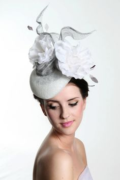 Staverton. A white sinamay beret with metallic silver floating streamers. With silver grey stripped feathers and luxurious white silk flowers.