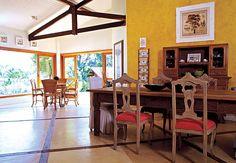 A cozinha desta casa de 276m², com balcão e armários brancos, fica ainda mais clara com os raios de sol que entram através da janela redonda, voltada para a rua.  O projeto é da arquiteta Claudia Haguiara