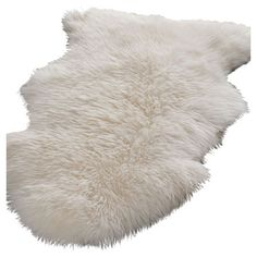Nimbus Sheepskin Rug at Joss & Main. In front of fireplace on white brick? White couch, white walls, glass coffee table with gold trim/accent, gold frame bookcase, accent chair w pops of beautiful color.