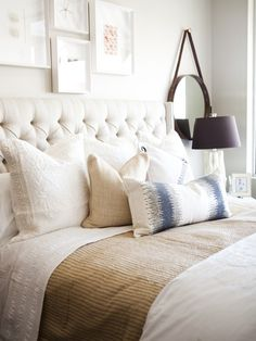 love everything....tufted headboard, circle mirror, framed art, pillows, and all the creamy colors.