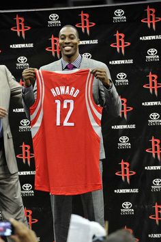 Dwight Howard holds up his new Rockets jersey.