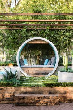Stunning modern garden design with a circular seat and bamboo all around.