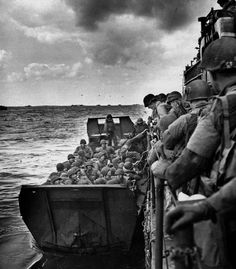 American troops clamber into a landing craft before hitting the beaches along France's Normandy coast in June 1944. The World War II operation was part of the massive Allied D-Day invasion to chase German forces out of France. An armada of landing vessels sits in the background under barrage balloons.