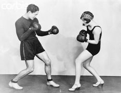 Photo shows Joan Crawford, Metro Goldwyn Mayer star, sparring with Gene Alsase, her trainer.
