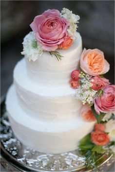 rose and ranunculus topped wedding cake