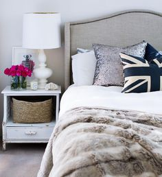 Fabulous bedroom with gray linen headboard with nailhead trim accented with metallic pillow, union jack pillow and faux fur throw blanket next to whitewashed bedside table filled with white table lamp, Chanel No. 5 art print and red roses.