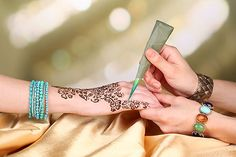 A henna artist at an Arabian Nights party. Find everything you need to plan your own party at http://sparklerparties.com/arabian-nights/henna-artist-at-arabian-nights-party