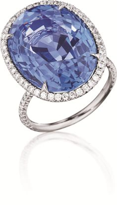 An Impressive Ceylon Sapphire and Diamond Ring  Set with an oval-cut unheated Ceylon sapphire, weighing approximately 22.56 carats, with a pavé-set diamond surround and half hoop, mounted in platinum, size 6. With report no.CS45916 dated 14 September 2011 from the American Gemological Laboratories, stating that the sapphire is of Sri Lanka (Ceylon) origin, with no indications of heat.