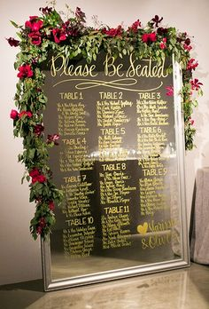 Brides: Calligraphy Mirror Seating Chart Display. This mirrored seating chart is decked out with gold calligraphy and a lush garland with bright red blooms.