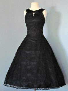 Lovely 1950's soft black lace tea-length party dress, with satin accents, satin banded neckline with rhinestone accents, low and square back, fitted bodice. No maker label.