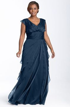 Diaphanous chiffon tiers overlay the dramatic floor-length skirt of a gown fashioned with a layered surplice bodice and an ultra-wide pleated band defining the Empire waist.
