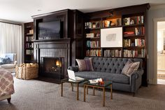 Love the whole wall of built-ins here, complete with fireplace and tufted sofa. Kristen Panitch Interiors