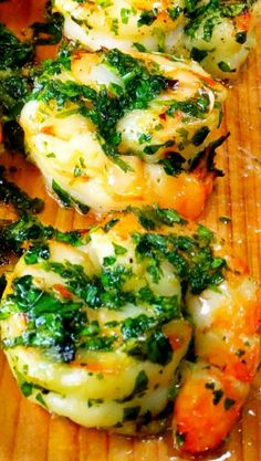 Cedar Planked Shrimp Recipe ~ The shrimp gets tossed in a light pesto made of parsley, garlic, lemon zest, olive oil and a pinch of red pepper flakes and then as it's cooking you brush even more of the pesto on, it's so good!
