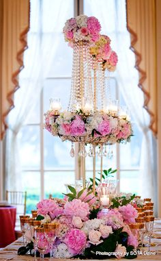 Custom crystal chandeliers and a garden of pink peony,hydrangea, and roses line this head table. Lush and Elegant!