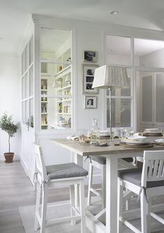 une verrière blanche et élégante sert de séparation entre la petite cuisine et la salle à manger