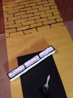 Yellow bulletin board paper, styrofoam packing material gouged out in a brick pattern. Paint the foam black and then stamp in desired pattern.