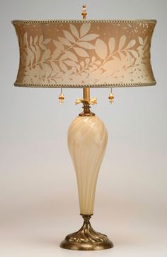 Lauren Table Lamp kn-kinzig-design-lighting-lauren-table-lamp-62s95 Creamy colored hand blown glass, with a latte and cream round shade, make this lamp a neutral lamp to put anywhere in your home. Copper and brass accents. hand crafted signature finial and pull. Double sockets Height listed does not include finial. 60-watt maximum bulb