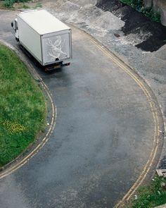 Ben Long, UK visual artist, creates drawings on the dust of panel trucks.