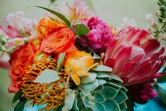 Bright bouquet with peonies, protea and succulents | Punch colored, rustic chic summer barn wedding | The Barn at Twin Oaks Ranch | Andrea Clark Photography