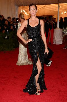 Gisele emitted a dark romantic glamour working a glittering Givenchy gown featuring a ruffle-trim thigh-baring slit.