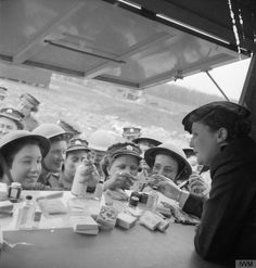 UK, WWII: At a YWCA mobile club, members of the ATS crowd up to the counter to buy cosmetics, tissues, sewing kits and notepaper. © IWM (D 13493)