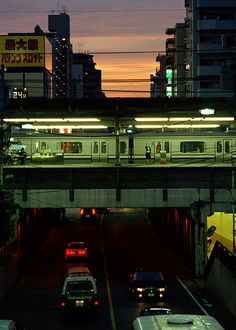 three levels and directions of action - at the top, the sun moving down; in the middle, the train moving through; at the bottom, the cars moving away.