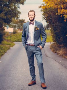 Guy in a blue gray suit with fall colors in his boutonniere and bow tie