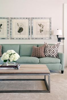 Love the frames above the couch, the coffee table and the flowers!