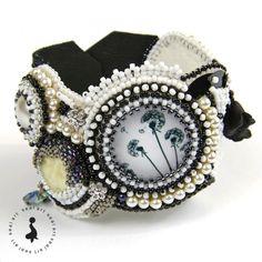 Wyjątkowa bransoletka w technice haftu koralikowego. Wykonana z koralików Toho i Delica, ze szklanym kaboszonem oraz wykonanymi przeze mnie kaboszonami Fimo – kaboszony są fluorescencyjne i dają niespodziewany efekt w ciemności. Wykończona perłami i kryształkami Swarovski. Zapinana na guzik w kształcie róży w kolorze srebrnym oraz pętelkę z koralików. Wykończona skórą naturalną. Idealny prezent na każdą okazję: urodziny, imieniny, walentynki, pod choinkę.