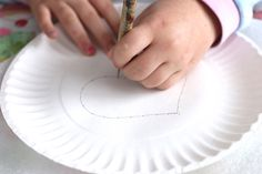 Poking holes in paper plate for kids beginner sewing project