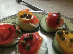 Cucumber slices, a bit of choice cream cheese, smoked salmon, tomato slices and capers.