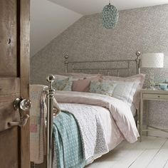 Pastel attic bedroom  With just one wall papered in a gentle design and in a pastel shade this small bedroom feels light and inviting. The bed is dressed with vintage quilts and eiderdowns for a cottage feel.  Chosen by Country Homes & Interiors