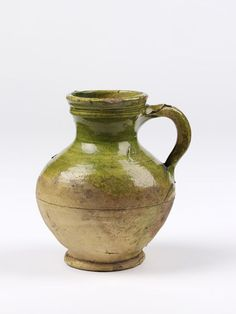 Jug of buff earthenware partly covered with a green glaze.  Place of Origin  Surrey, England (possibly, made) Hampshire, England (possibly, made) Date  ca. 1575-1625 (made)