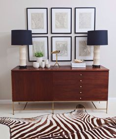interior design: mid century style teak sideboard console with brass legs, bamboo table lamps, framed map prints, brass binoculars, zebra animal hide rug
