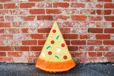DIY Pizza Slice Piñata MATERIALS: 3-4 large pieces of plain cardstock 1 packet orange crepe paper 1 packet yellow crepe paper colored card for pizza toppings (we used red, green, light green and gold) double-sided tape sticky tape pencil scissors string for hanging