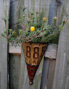 An old license plate is bent, shaped, and upcycled into a rustic wall planter. License plates never looked so good.