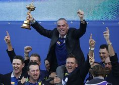 Captain of Team Europe Paul McGinley of Ireland (top) holds the trophy as he celebrates with his players after retaining the Ryder Cup on the final day of the Ryder Cup golf tournament at the Gleneagles Hotel in Gleneagles, Scotland, on September 28, 2014. Jamie Donaldson grabbed the crucial point Paul McGinley's side needed for the win when he defeated Keegan Bradley 4 and 3 in the 10th of the closing 12 singles