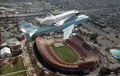 """Retired space shuttle Endeavour, atop its 747 """"taxi,"""" flies over Los Angeles Coliseum on its way to LAX. From there it will travel by land to its new, and final, home at the California Science Center."""