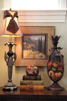 In a basket. Of course, other containers work as well, like this basket. Whether those pumpkins are a seasonal addition or stay year-round, they definitely prove to be a warm, colorful addition to the vignette.
