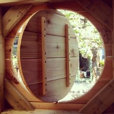 a circular pivoting window of a tree fort on Gardenista