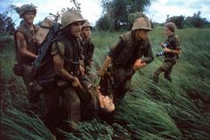 """""""Four Marines recover the body of a fifth as their company comes under fire near Hill 484."""" Vietnam, October 1966. NOTE: At right is the French-born photojournalist Catherine Leroy (1945 - 2006); she was cropped out of the version of this photo that originally ran in LIFE. Caption from LIFE."""