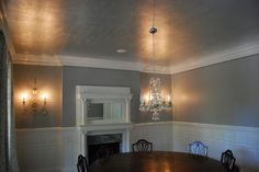 Silver leaf ceiling with large round dining room table