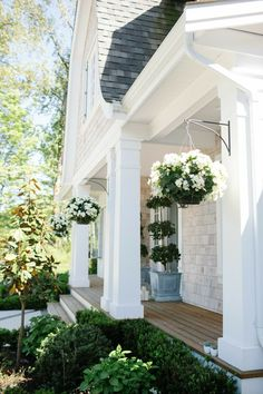 Like the wood decking, square columns plus gorgeous flowers. Very inviting.