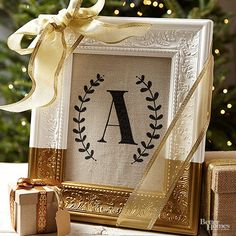 A gilded frame and bold monogram makes this a stunning holiday gift. We like to place it on a shelf or bookcase for maximum impact. To create, paint the frame white and let dry. Paint the bottom third of the frame gold and let dry. Using stencils, paint a letter and border onto cut fabric. Frame the fabric and wrap with a gold ribbon.